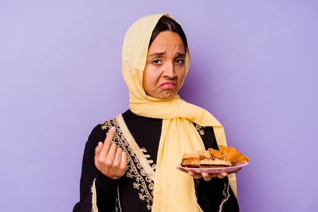 Молодая марокканская женщина держит арабские сладости, изолированные на фиолетовом фоне, указывая пальцем на вас, как будто приглашая подойти ближе.