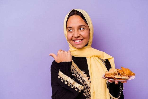 멀리 엄지 손가락으로 보라색 배경 포인트에 고립, 웃음과 평온한 아라비아 과자를 들고 젊은 모로코 여자.