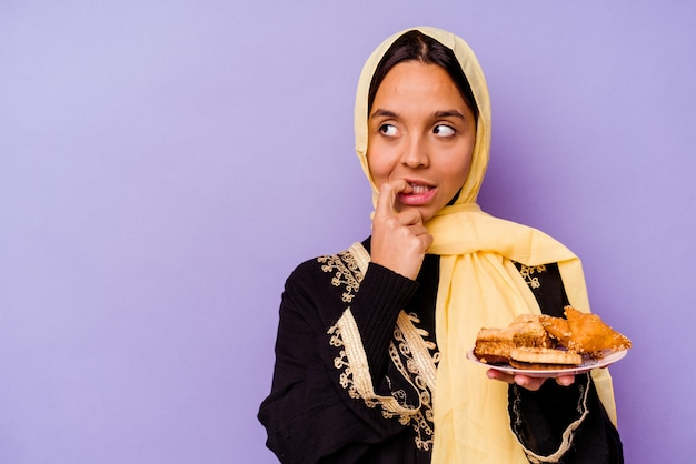 보라색 배경에 고립 된 아라비아 과자를 들고 젊은 모로코 여자 복사본 공간을보고 뭔가 대 한 생각을 편안 하 게.