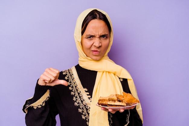 젊은 모로코 여자 싫어하는 제스처를 보여주는 보라색 배경에 고립 된 아라비아 과자를 들고 아래로 엄지 손가락. 불일치 개념.