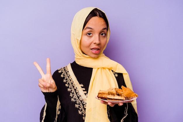 Молодая марокканская женщина, держащая арабские сладости, изолированные на фиолетовом фоне, показывает номер два пальцами.