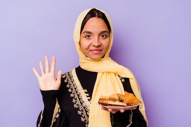 보라색 배경에 고립 아라비아 과자를 들고 젊은 모로코 여자 손가락으로 명랑 게재 번호 5 웃 고.
