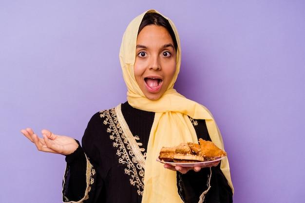 보라색 배경에 고립 아라비아 과자를 들고 젊은 모로코 여자 놀라게 하 고 충격.
