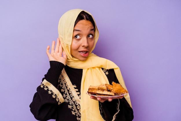 Молодая марокканская женщина, держащая арабские сладости, изолированные на фиолетовом фоне, пытается слушать сплетни.