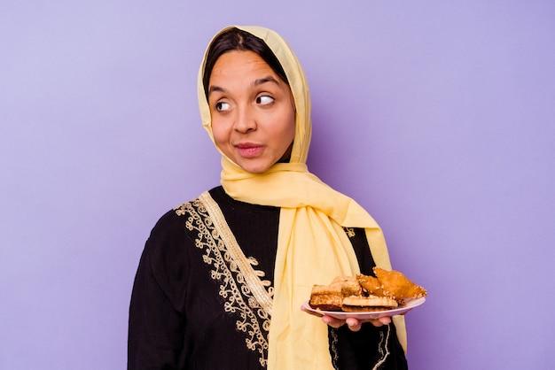 Молодая марокканская женщина, держащая арабские сладости, изолированные на фиолетовой стене, смотрит в сторону, улыбаясь, веселая и приятная.