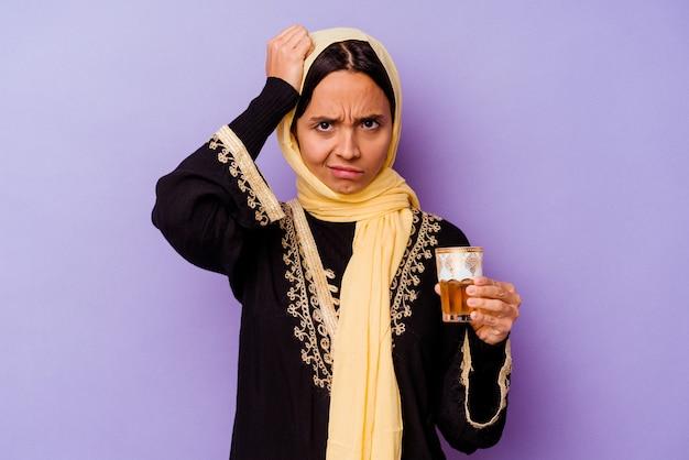 충격을 받고 보라색 배경에 고립 된 차 한 잔을 들고 젊은 모로코 여자, 그녀는 중요한 회의를 기억했습니다.