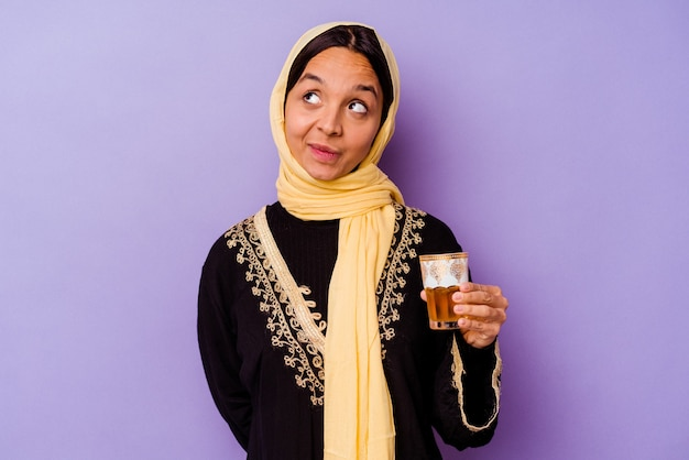 목표와 목적을 달성하는 꿈 보라색 배경에 고립 된 차 한 잔을 들고 젊은 모로코 여자