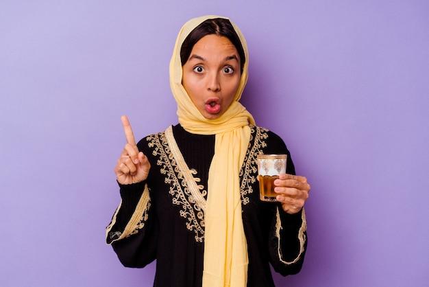 몇 가지 좋은 아이디어, 창의성의 개념 데 보라색 배경에 고립 된 차 한 잔을 들고 젊은 모로코 여자.