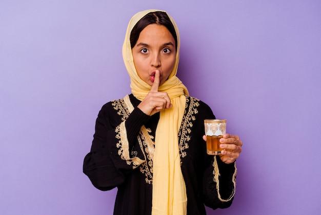 비밀을 유지하거나 침묵을 요구하는 보라색 배경에 고립 된 차 한 잔을 들고 젊은 모로코 여자.