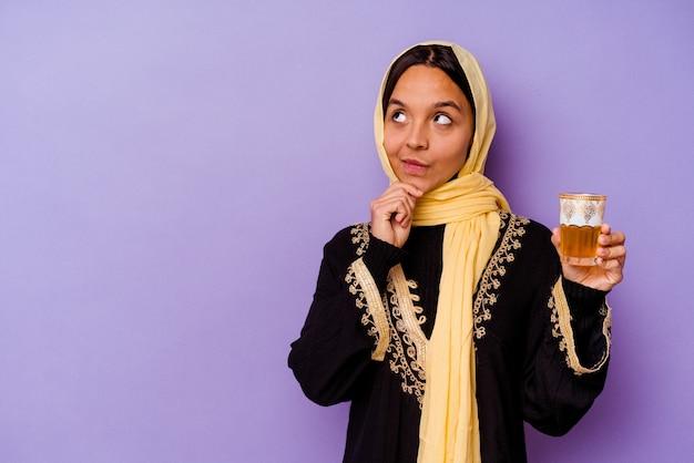 의심스럽고 회의적인 표정으로 옆으로 찾고 보라색 배경에 고립 된 차 한 잔을 들고 젊은 모로코 여자.