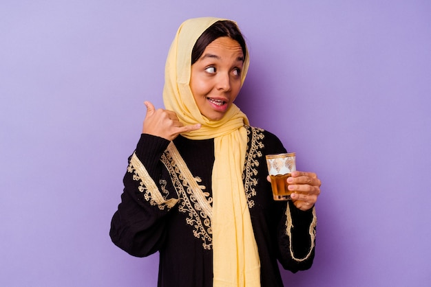 손가락으로 휴대 전화 제스처를 보여주는 보라색 배경에 고립 된 차 한 잔을 들고 젊은 모로코 여자.