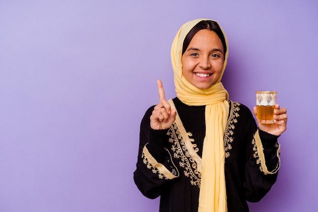 손가락으로 번호 하나를 보여주는 보라색 배경에 고립 된 차 한 잔을 들고 젊은 모로코 여자.