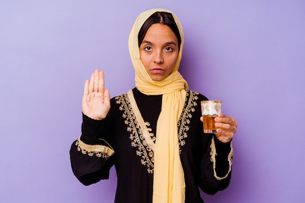 당신을 방지하는 정지 신호를 보여주는 뻗은 손으로 서 보라색 배경에 고립 된 차 한 잔을 들고 젊은 모로코 여자.