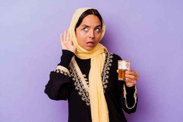 Молодая марокканская женщина, держащая стакан чая, изолированные на фиолетовом фоне, пытается слушать сплетни.