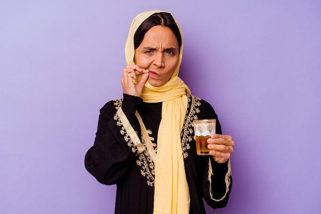 비밀을 유지하는 입술에 손가락으로 보라색 배경에 고립 된 차 한 잔을 들고 젊은 모로코 여자.