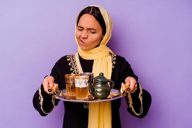 보라색 배경에 고립 된 차 한 잔을 들고 젊은 모로코 여자