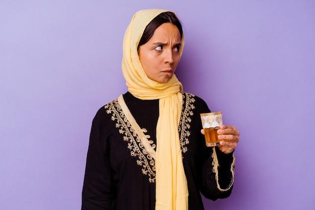 Молодая марокканская женщина, держащая стакан чая, изолированного на фиолетовой стене, смущена, чувствует себя сомнительной и неуверенной.