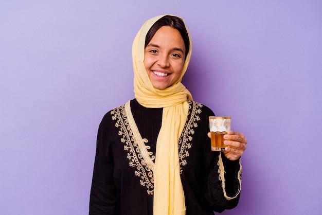 Молодая марокканская женщина, держащая стакан чая, изолированного на фиолетовой стене, счастлива, улыбается и жизнерадостна.