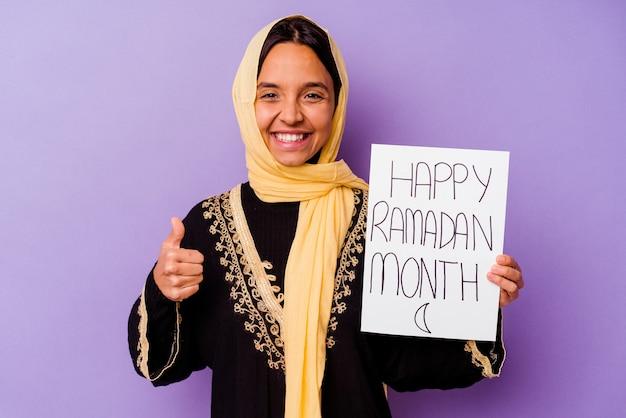 보라색 배경에 고립 된 행복 라마단 현수막을 들고 젊은 모로코 여자