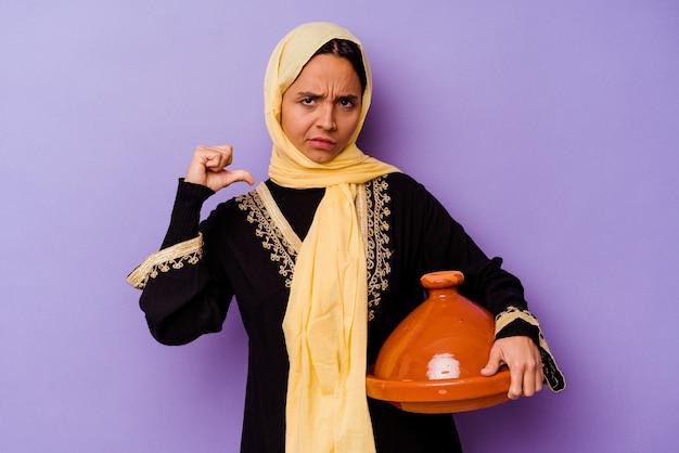 보라색 배경에 고립 된 tajine을 들고 젊은 모로코 여자는 자랑스럽고 자신감을 느낍니다.