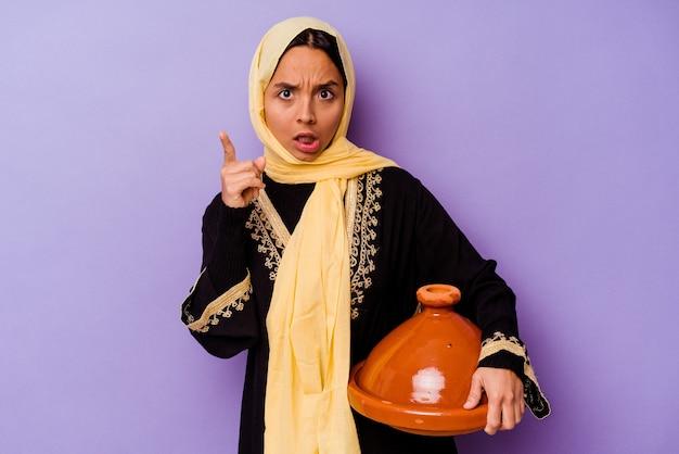 아이디어, 영감 개념 데 보라색 배경에 고립 된 tajine를 들고 젊은 모로코 여자.