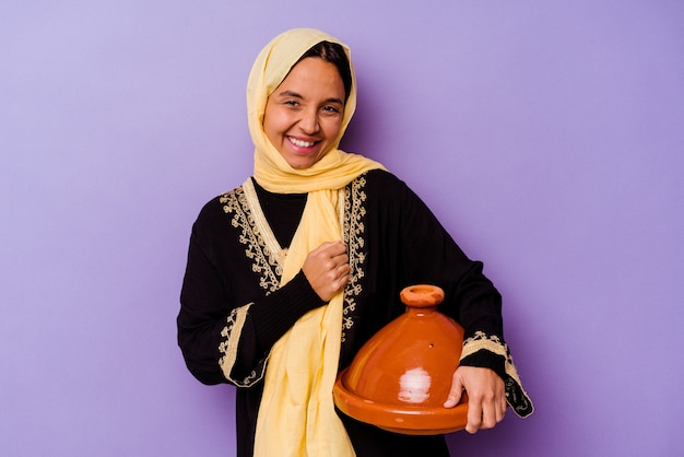 보라색 배경 웃음과 재미에 고립 된 tajine를 들고 젊은 모로코 여자.