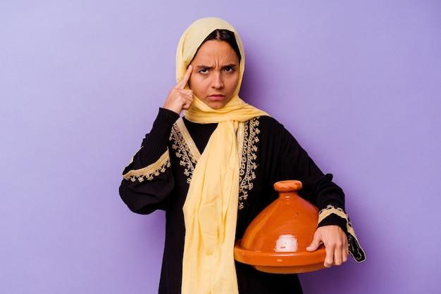 생각, 작업에 초점을 맞춘 손가락으로 사원을 가리키는 보라색 배경에 고립 된 tajine를 들고 젊은 모로코 여자.
