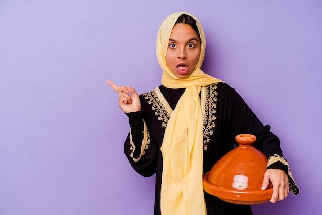 측면을 가리키는 보라색 배경에 고립 된 tajine을 들고 젊은 모로코 여자