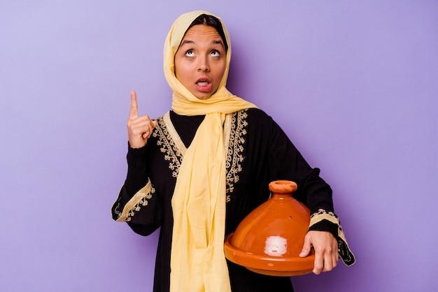 열린 된 입으로 거꾸로 가리키는 보라색 배경에 고립 된 tajine를 들고 젊은 모로코 여자.