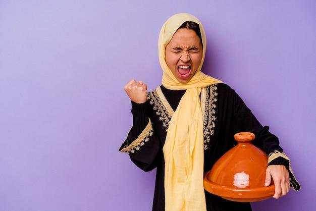 승리, 승자 개념 후 주먹을 올리는 보라색 배경에 고립 된 tajine를 들고 젊은 모로코 여자.
