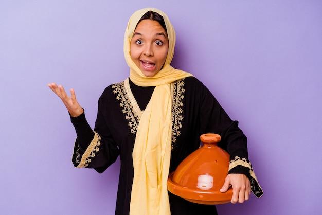 즐거운 놀라움을 받고, 흥분하고 손을 올리는 보라색 배경에 고립 된 tajine을 들고 젊은 모로코 여자.