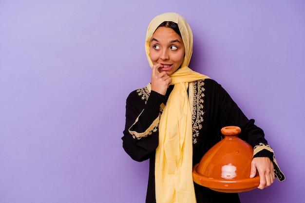 보라색 배경에 고립 된 tajine을 들고 젊은 모로코 여자 복사본 공간을 찾고 뭔가에 대해 편안한 생각.