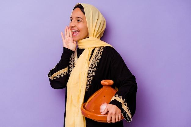 보라색 배경 소리와 열린 된 입 근처 손바닥을 들고에 고립 된 tajine를 들고 젊은 모로코 여자.