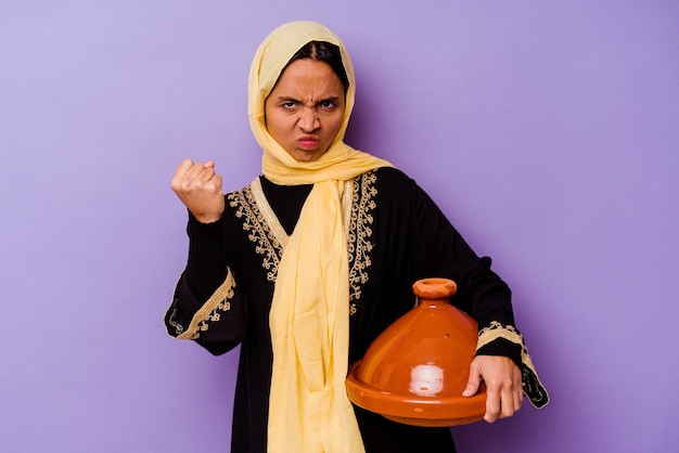 Молодая марокканская женщина, держащая таджин, изолирована на фиолетовом фоне, показывая кулак в камеру, агрессивное выражение лица.