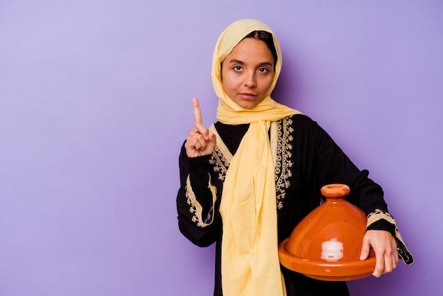 손가락으로 번호 하나를 보여주는 보라색 배경에 고립 된 tajine를 들고 젊은 모로코 여자.