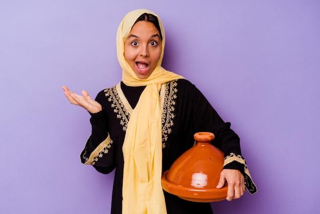 보라색 배경에 고립 된 tajine을 들고 젊은 모로코 여자 놀라게 하 고 충격.