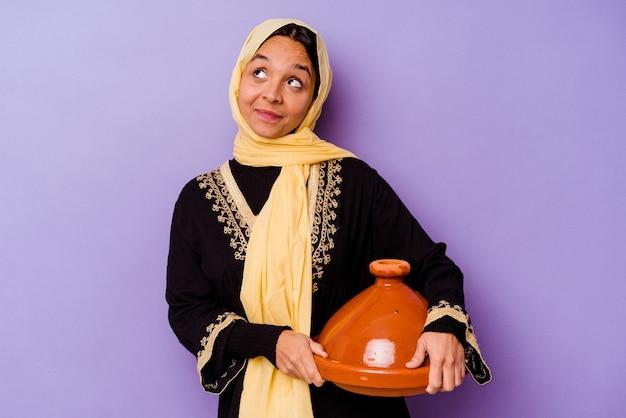 Молодая марокканская женщина, держащая таджин на фиолетовой стене, мечтающая о достижении целей и задач
