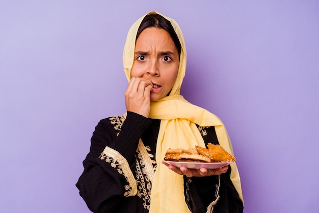 Young moroccan woman holding a arabian sweets isolated on purple background biting fingernails, nervous and very anxious.
