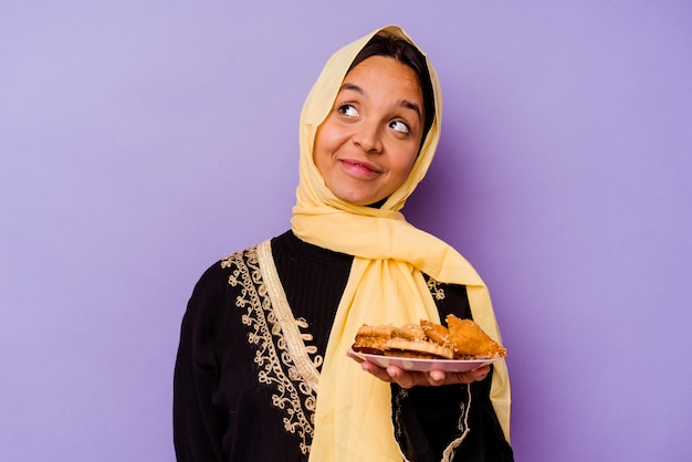 Young moroccan woman holding a arabian sweets isolated on purple background dreaming of achieving goals and purposes