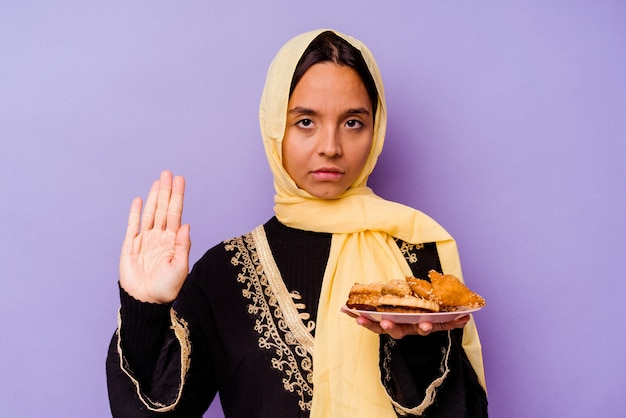 Young moroccan woman holding a arabian sweets isolated on purple wall standing with outstretched hand showing stop sign, preventing you.