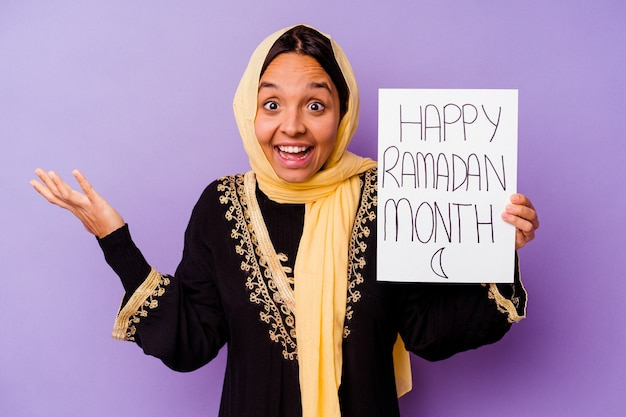 Young moroccan woman holding a happy ramadan placard isolated on purple wall