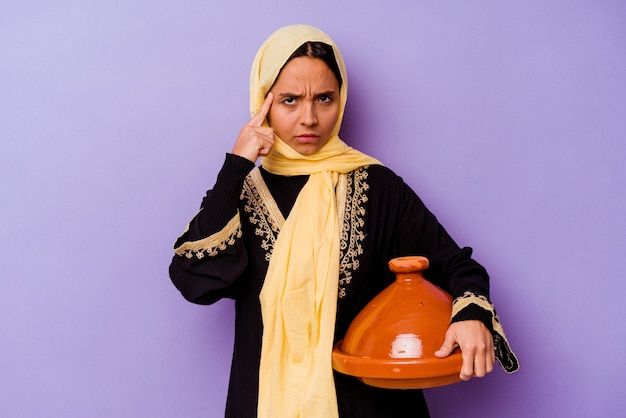 Young moroccan woman holding a tajine isolated on purple background pointing temple with finger, thinking, focused on a task.