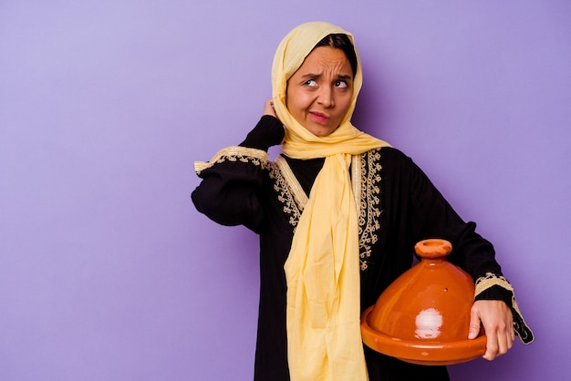 Young moroccan woman holding a tajine isolated on purple background touching back of head, thinking and making a choice.