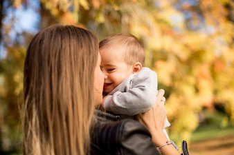 Young mother and baby boy in autumn park