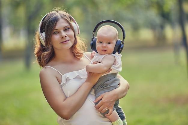 若い母親と男の子はワイヤレスヘッドフォンで音楽を聴きます