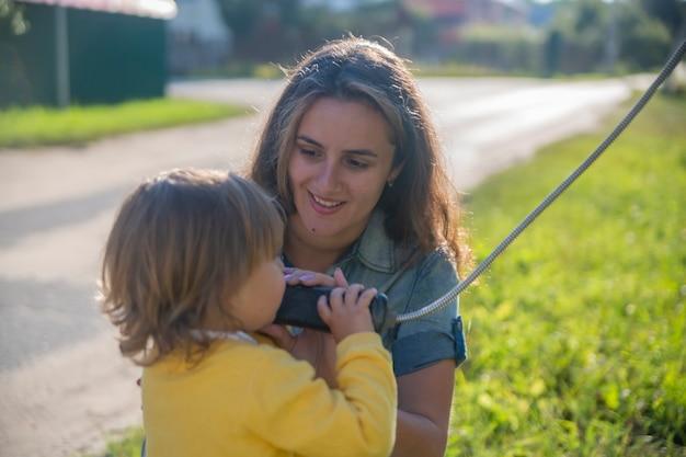 Молодая мать и ребенок звонят по стационарному уличному телефону в телефонной будке в деревне летом. прогулки с семьей летний солнечный день в лучах солнца. художественная направленность
