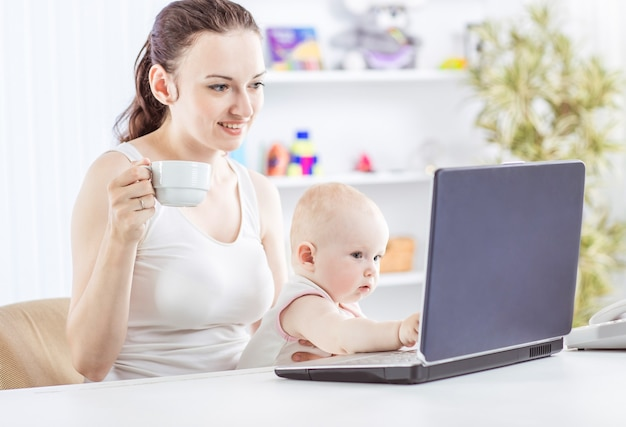 ラップトップを使用しておばあちゃんと通信する若い母親と赤ちゃん