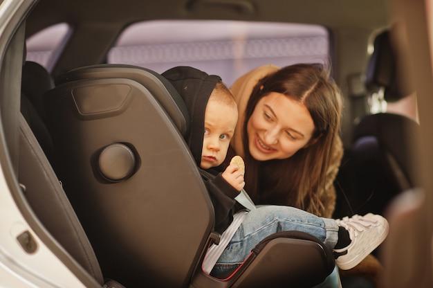 Молодая мать и ребенок в машине. детское кресло на стуле. концепция безопасности вождения.