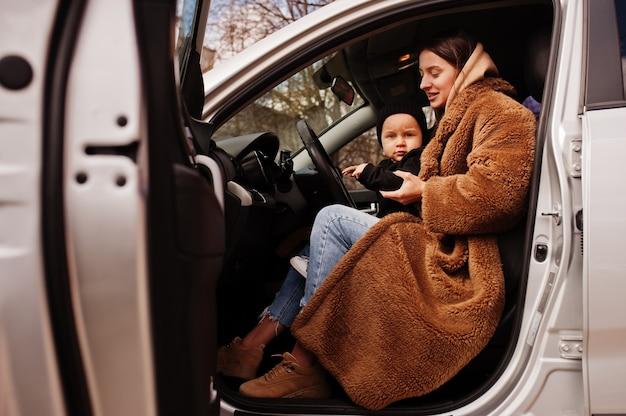 젊은 엄마와 차에 아이입니다. 안전 운전 개념입니다.