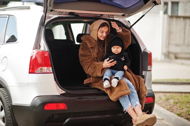 젊은 엄마와 아이가 차 트렁크에 앉아 휴대전화를 보고 있습니다. 안전 운전 개념입니다.